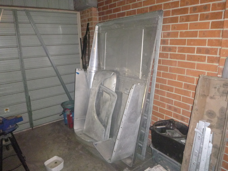 Roof, guards, and rear tailgate leaning against wall of garage