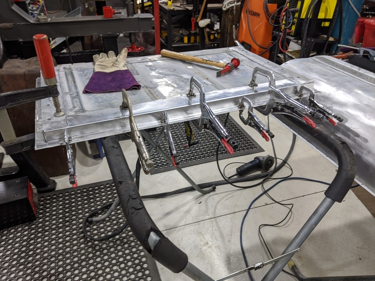 Rear tailgate with replacement piece held in by clamps